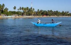 渔夫用浆划他们的舷外架小船 免版税图库摄影