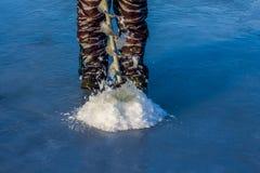渔夫钻井在冰的一个孔 免版税库存图片
