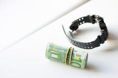 滚动的捆绑与在白色背景隔绝的现代手表的一百欧元笔记 图库摄影