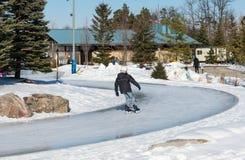 滑冰在一串冰冷的足迹的年轻男孩 图库摄影