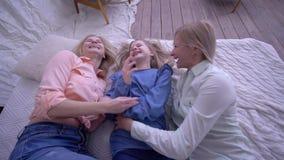 滑稽的家庭、愉快的母亲有成人的和小的女儿秋天在床上在乐趣笑和痒感女孩期间