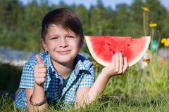 滑稽的男孩用西瓜在夏天公园显示赞许 库存照片