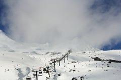 滑雪者、使用电车或滑雪电缆车的挡雪板和游人到积雪的迷雾山脉的上面 库存照片