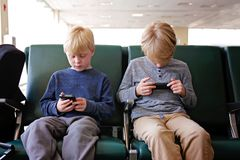 演奏在他们的手机的两个孩子,当等待飞机在机场时 免版税图库摄影