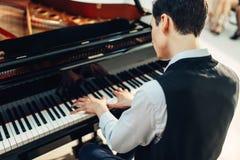 演奏在大平台钢琴的钢琴演奏家音乐 免版税库存图片