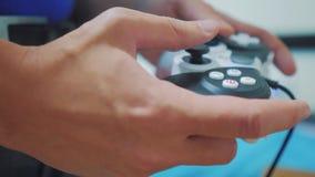 演奏在电视的人gamepad手录影控制台 手拿着演奏在电视的新的控制杆录影控制台 游戏玩家戏剧比赛与 股票视频
