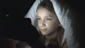 演奏片剂在黑暗的夜,女孩浏览互联网的孩子在床上,不睡觉 库存照片