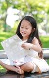 演奏贴纸的愉快的矮小的亚裔儿童女孩在绿色公园 免版税图库摄影