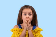 演播室射击了有佩带在蓝色背景的害怕眼睛的一女孩黄色sundress 她站立吓唬  免版税库存照片