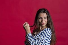 演播室被射击一可爱的美女被隔绝对空的红色演播室墙壁 库存照片