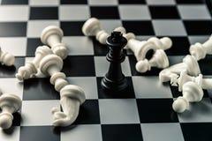 染黑董事会企业检查棋结尾的游戏高亮度显示损失伙伴黑白照片采取白色在方法成功的隐喻 在对手的被击败的白色棋的中黑人国王 免版税库存照片