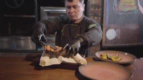 服务在木头的黑手套的厨师烹调了可口水多的鱼用烤甜椒,辣椒和 影视素材