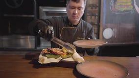 服务在木头的黑手套的厨师烹调了可口水多的鱼用烤甜椒,辣椒和 股票录像