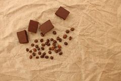 挤奶与咖啡豆的多孔巧克力甜点在亚麻制纹理背景 免版税库存照片