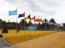 挥动在联合国纪念公墓中天空的国旗在釜山,韩国,亚洲 库存图片