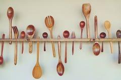 木厨房工具:木匙子,木叉子,木小铲,在白色墙壁上垂悬 免版税图库摄影
