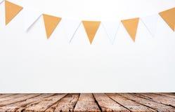 木桌和垂悬的纸旗子在白色墙壁背景,装饰项目党的,节日,庆祝事件 免版税库存照片