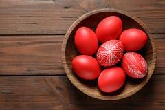 木碗用在桌,顶视图上的被绘的红色复活节彩蛋 免版税库存图片