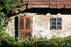 木门和窗口登上与装饰生锈的金属铰链在小被放弃的家庭房子被毁坏的墙壁与 库存照片