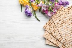 未发酵的面包和花的平的被放置的构成在木背景 逾越节Pesach Seder 库存照片