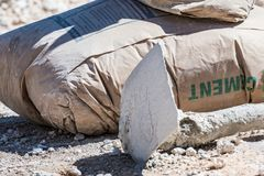 未打开的棕色水泥袋子和一把锄在地面上 免版税库存照片
