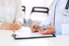未知的妇女医生和女性患者谈论某事,当站立在总台附近在紧急医院时 免版税库存图片