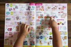 指向她的在玩具'R'美国小册子的梦想玩具的儿童手 库存照片