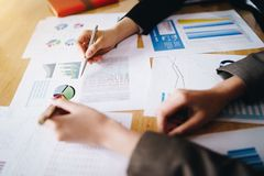 指向在商业文件的女实业家笔候选会议地点 讨论和分析显示结果的数据图和图表 免版税库存图片