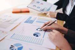 指向在商业文件的女实业家笔候选会议地点 讨论和分析显示结果的数据图和图表 免版税库存照片