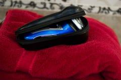 有三把刀片的电蓝色转台式剃具在黑盒和毛巾附近 免版税库存图片