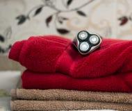 有三把刀片的电蓝色转台式剃具在黑盒和毛巾附近 库存照片