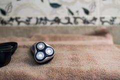 有三把刀片的电蓝色转台式剃具在黑盒和毛巾附近 库存图片