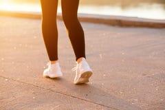 有一个微小,肌肉图的一名妇女在黑体育衣裳和白色运动鞋到处乱跑本质上 播种的照片 免版税库存图片