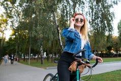有一个自行车身分的时髦的女孩在微笑的公园看和 妇女在公园骑一辆自行车 库存照片