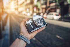 有一台减速火箭的照相机的人的手 免版税库存照片