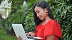 有一台膝上型计算机的年轻印度尼西亚女孩在手中在公园 股票视频