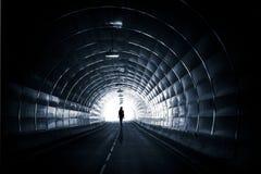 有一名走的妇女的黑暗的隧道 免版税库存照片