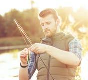 有一条转动和诱饵捉住的鱼的渔夫在湖或河 人与一条钓鱼的路的一个周末 爱好和 免版税库存照片