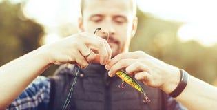 有一条转动和诱饵捉住的鱼的渔夫在湖或河 人与一条钓鱼的路的一个周末 爱好和 免版税库存图片