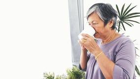 有一杯咖啡的不快乐的孤独的亚裔资深妇女单独在家,慢动作 影视素材