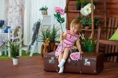 有一朵花的女孩在手提箱 免版税库存图片