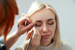 有一把刷子的化妆师在有一个平的边缘的手上绘在模型的眼皮的箭头,申请构成于眼睛 库存图片
