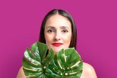 有一片棕榈叶的美丽的年轻女人在明亮的背景 免版税库存照片