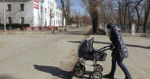 有一辆婴儿推车的妈妈在公园 股票录像
