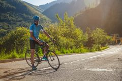 有一辆自行车的一个人在山 在用森林盖的山的路 免版税库存图片