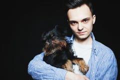 有他的狗的年轻人在黑背景 图库摄影