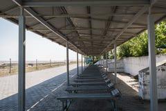 有太阳懒人和灯笼的老生锈的太阳机盖在海散步 免版税库存照片