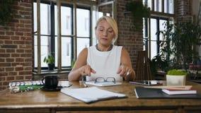 有头疼的一名可爱的白种人妇女完成工作在书桌并且取消玻璃 影视素材