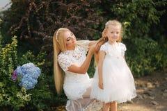 有女儿的妈妈白色礼服的在公园花费时间 金发女性 母亲编织猪尾女儿外部 库存照片