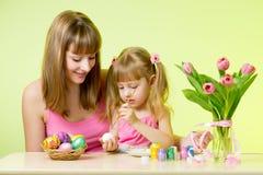 有她的在家上色复活节彩蛋的妈妈的儿童女孩 免版税库存图片
